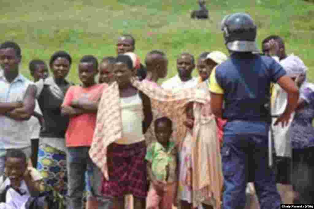 Des gens sont rassemblés à l'exterieur, lors du procès des rebelles présumés ADF, à Beni, RDC, le 24 août 2016. (VOA/Charly Kasereka)