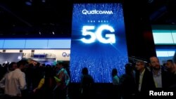 ປະຊາຊົນຍ່າງຜ່ານ ວິດີໂອ ທີ່ສະແດງໃຫ້ເຫັນການສົ່ງເສີມການເຊື່ອມຕໍ່ 5G ຢູ່ຕູ້ວາງສະແດງຂອງບໍລິສັດ Qualcomm ໃນງານວາງສະແດງ CES 2019. ນະຄອນ ລາສ ເວກັສ, ລັດ ເນວາດາ. 8 ພຶດສະພາ, 2019.