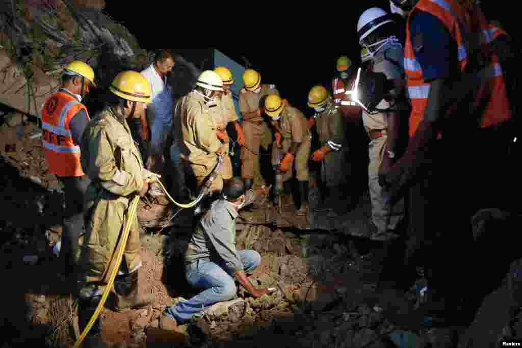 Rescue workers attempt to remove the body of a victim at the site of a collapsed building that was under construction, Canacona, India, Jan. 5, 2014.