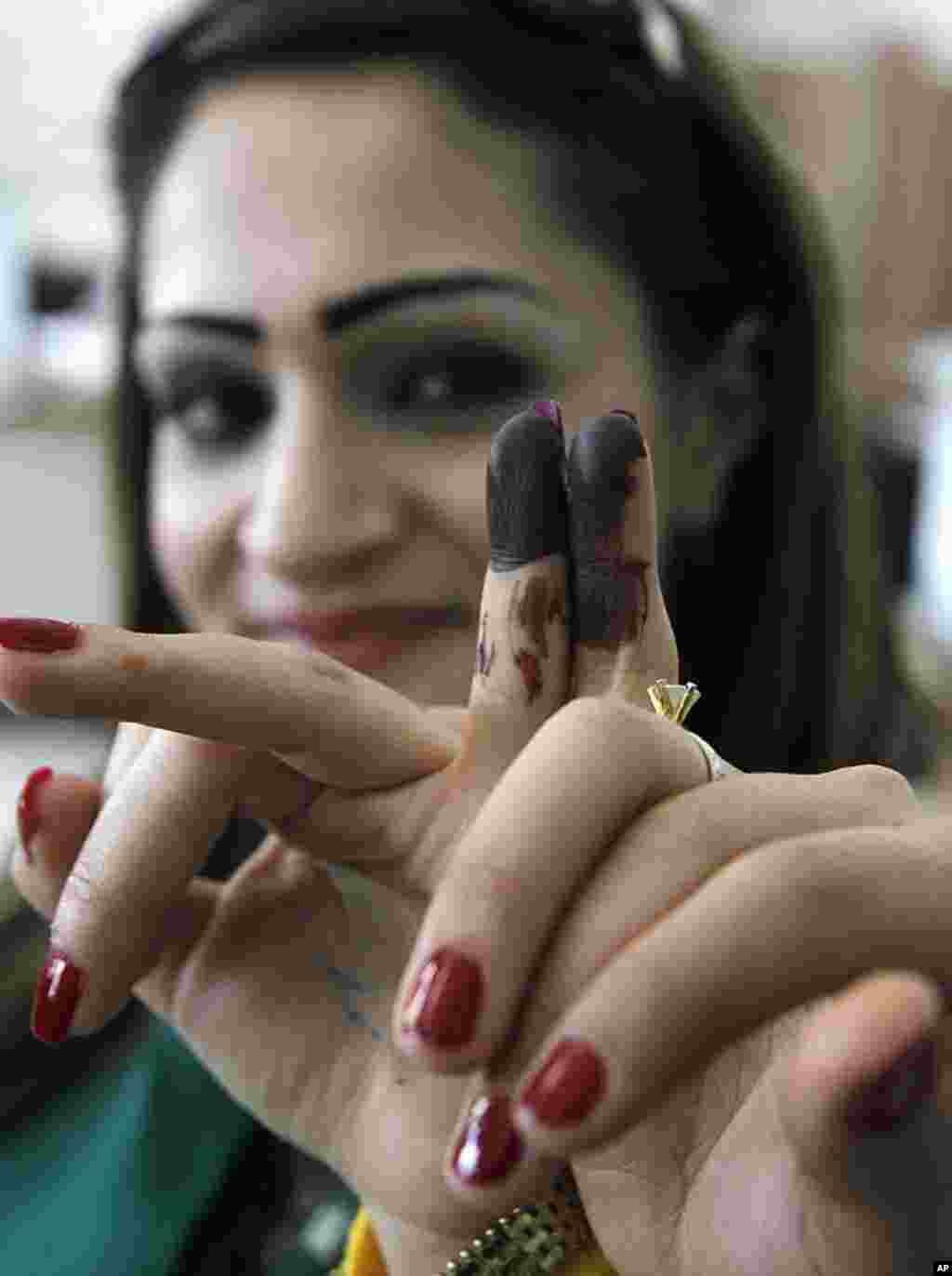 Two Syrian women display their stained fingers after voting in parliamentary elections in Damascus, May 7, 2012. (Reuters)