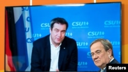 FILE PHOTO: Christian Social Union (CSU) Bavarian State Prime Minister Markus Soeder is seen on a screen as he speaks to Christian Democratic Union (CDU) North Rhine Westphalia (NRW) State Prime Minister Armin Laschet during a virtual CDU new year recepti