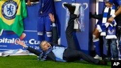 L'entraîneur-chef de Chelsea, José Mourinho, couché sur la pelouse, célèbre la victoire de son équipe à la finale de la Coupe de la Ligue anglaise à la fin du match entre Chelsea et Tottenham, au stade de Wembley à Londres, 1er mars 2015.