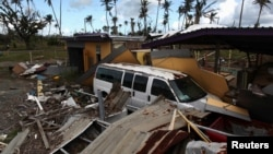 A car is partially buried under the remains of a building, after Hurricane Maria hit the island in September, in Humacao, Puerto Rico, Jan. 25, 2018.
