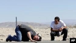 Ron Mikulaco, a la izquierda, se agacha para ver una grieta causada por un terremoto junto a su sobrino Brad Fernández en la carretera 178 el sábado 6 de julio de 2019, en las afueras de Ridgecrest, California.