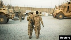 A U.S. soldier from the 3rd Cavalry Regiment walks with the unit's Afghan interpreter in Afghanistan, Dec. 11, 2014. An interpreter for U.S. military forces survived the war in Afghanistan only to be injured in an attack in a city in Oregon.