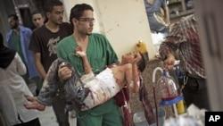 Một bác sĩ, tại một bệnh viện ở Aleppo, bế một thiếu niên bị thương nặng vì đạn pháo kích của Syria, 4/10/12