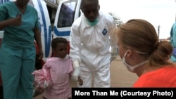 More Than Me's focus temporarily shifted from education to emergency health care as the Eboloa crisis peaked in Liberia. A health worker and Katie Meyler, crouching, reassure a young girl in Monrovia.
