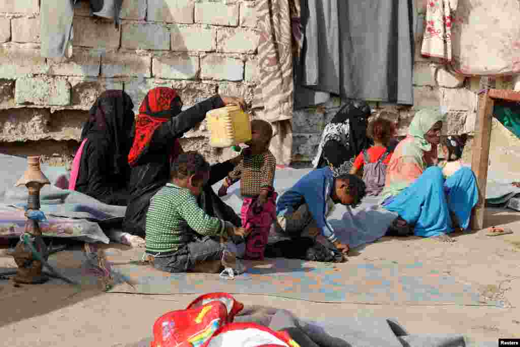Internally displaced people sit at a makeshift camp for IDPs in al-Jarahi, south of the Red Sea port city of Houdieda, Yemen.