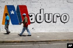 Supporters of Venezuela's President Nicolas Maduro walk past a campaign mural before a rally with him, in Charallave, Venezuela, May 15, 2018.