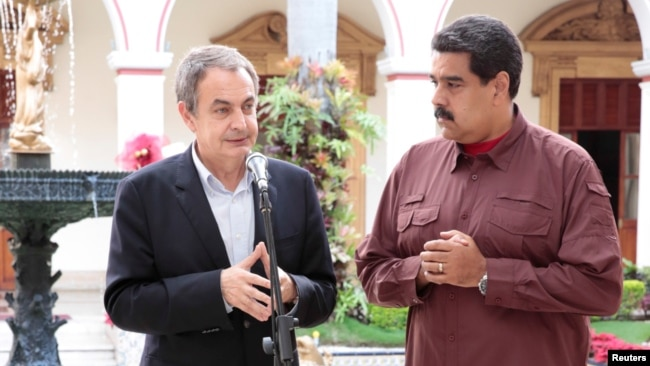 FILE - Former Spanish prime minister Jose Luis Rodriguez Zapatero, left, talks next to Venezuela's President Nicolas Maduro after their meeting at Miraflores Palace, in Caracas, Venezuela, Nov. 23, 2016.