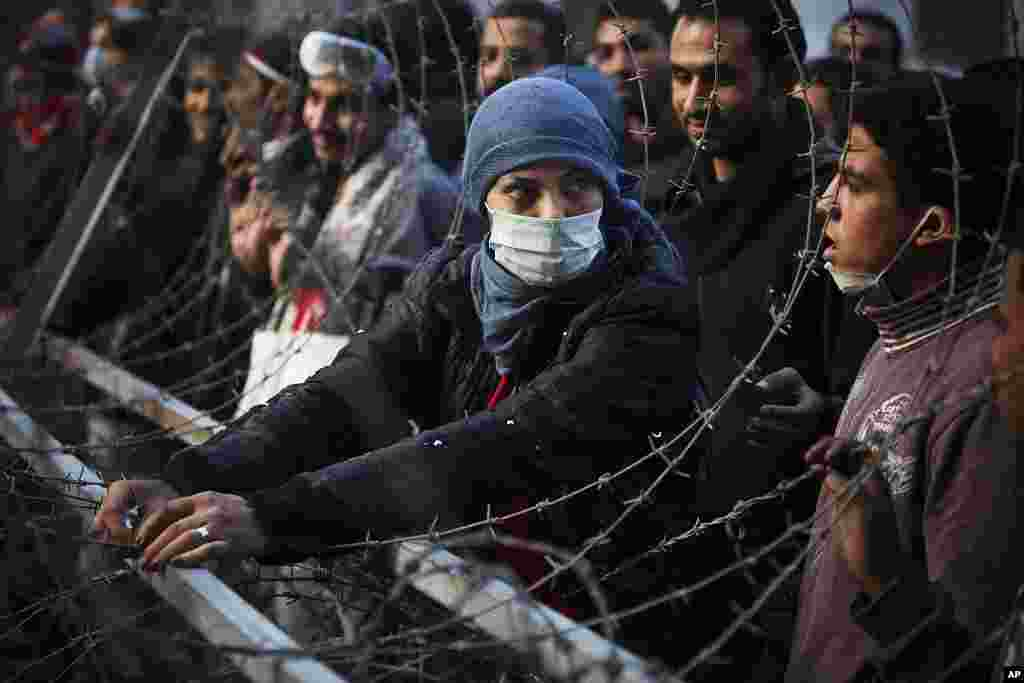 A woman protester attempts to dismantle a barbed wire barricade, newly erected by the Egyptian army, near Tahrir square in Cairo, November 24, 2011. (AP)