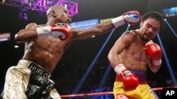 Manny Pacquiao (kanan) dalam pertarungan dengan Floy Mayweather, Sabtu (2/5) di Las Vegas. (AP/John Locher)