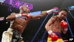 "Floyd Mayweather (kiri) memukul Manny Pacquiao dalam ""Pertarungan Abad Ini"" di Las Vegas (2/5). (AP/John Locher)"