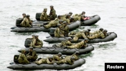 Japan Self-Defense Force (JSDF) soldiers ride rubber boats as they move toward Eniyabanare Island during military exercises, near the town of Setouchi on the southern Japanese island of Amami Oshima, Kagoshima prefecture, May 22, 2014.