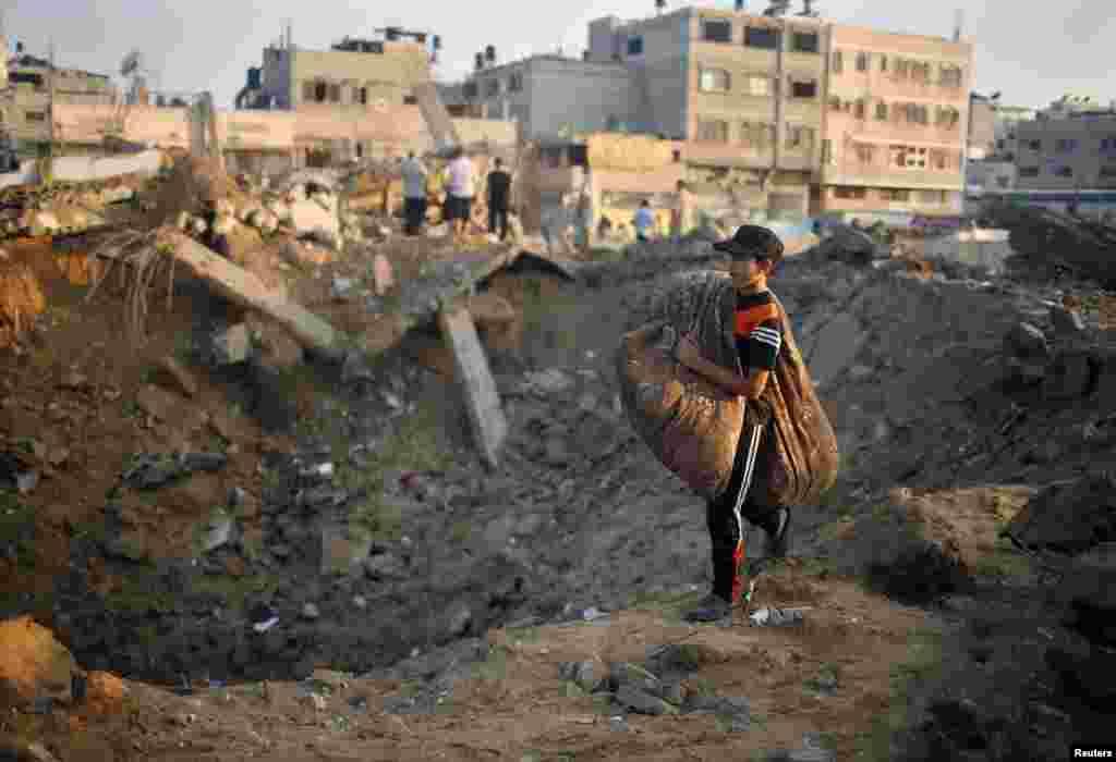 ایک فلسطینی بچہ تباہ حال عمارت کے پاس سے گزر رہا ہے۔