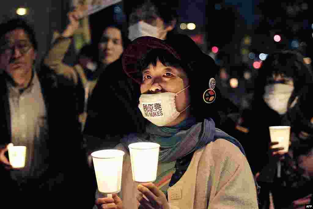 Женщина в маске с надписью «Нет - АЭС» на церемонии, посвященной 25-летней годовщины аварии в Чернобыле. Токио. 26 апреля 2011 г.