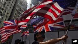 Seorang pedemo mengibarkan bendera AS dan Inggris saat berpawai ke kantor polisi Tsim She Tsui di Hong Kong, 20 Oktober 2019.