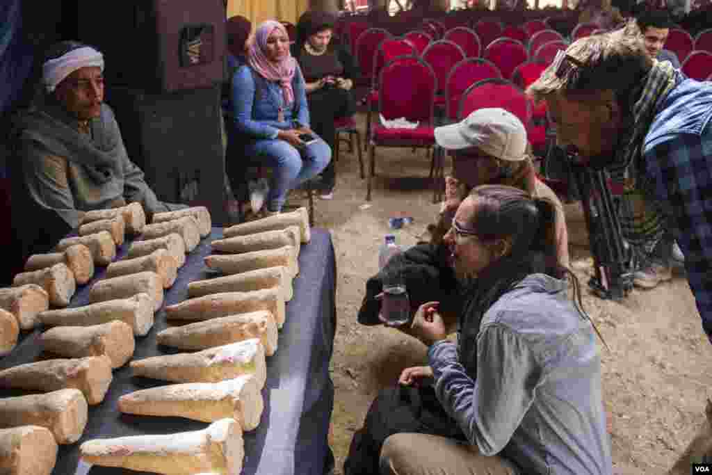 Tourists look at 100 funerary cones on display found in the tomb of Kampp 150 in the Draa Abul Naga necropolis on Luxor's west bank, Egypt, Dec. 9, 2017. Such cones were generally placed on outer walls of tombs, above the entrance. (H. Elrasam/VOA)