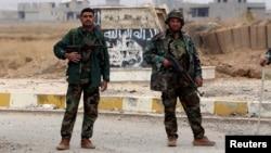 Chiến binh người Kurd đứng trên đường phố ở thành phố Sinjar, miền Bắc Iraq.