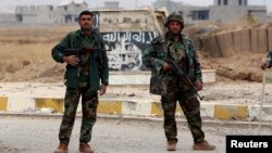 FILE - Kurdish Peshmerga fighters stand in a street against the backdrop of a defaced Islamic State flag in the town of Sinjar, northern Iraq, Nov. 16, 2015.
