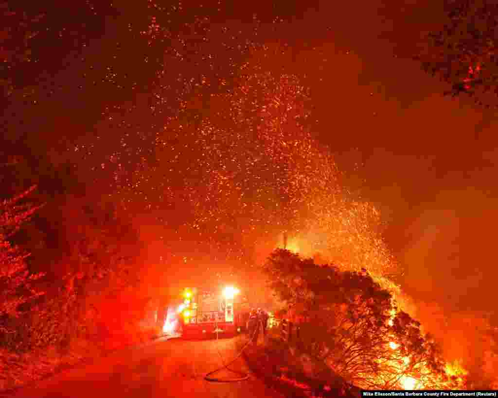 Firefighters battle flames off Highway 154 north of Santa Barbara, California, Nov. 25, 2019, in this picture obtained from social media.