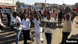 Hundreds of protesters, some carrying placards, chanted anti-government slogans before clashing with riot policemen in Burundi's capital, Bujumbura, April 28, 2015.