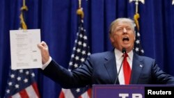 U.S. Republican presidential candidate, real estate mogul and TV personality Donald Trump holds up his financial statement showing his net worth as he formally announces his campaign for the 2016 Republican presidential nomination in New York, June 16, 20