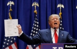 U.S. Republican presidential candidate, real estate mogul and TV personality Donald Trump holds up his financial statement showing his net worth as he formally announces his campaign for the 2016 Republican presidential nomination in New York, June 16, 2015.