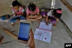 Murid-murid SD di desa bukit Temulawak, Daerah Istimewa Yogyakarta, sedang belajar secara online menggunakan ponsel pintar. (Foto ilustrasi: AFP)
