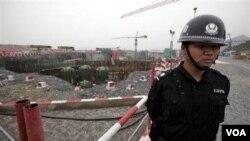 Seorang polisi Tiongkok menjaga konstruksi PLTN di Sanmen, provinsi Zhejiang (foto: dok). Tiongkok membekukan kontruksi PLTN setelah bencana di PLTN Fukushima, Jepang.