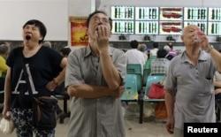 在武汉的证券交易市场,股民们看着电脑屏幕上的股市行情(2015年7月3日)
