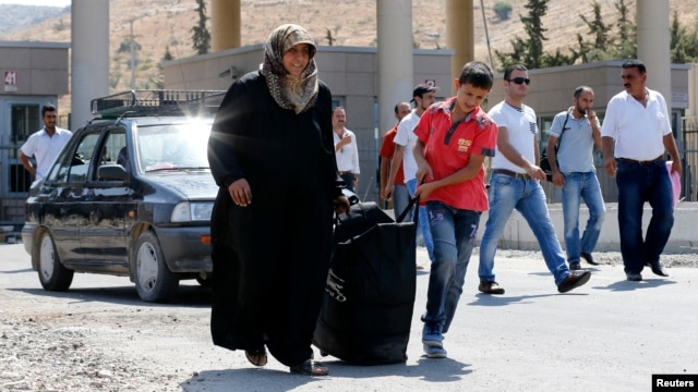 Syrian people carry their belongings as they enter Turkey with their family from the Turkish Cilvegozu border gate, located opposite Syrian commercial crossing point Bab al-Hawa in Reyhanli, Hatay province, Sept. 4, 2013.