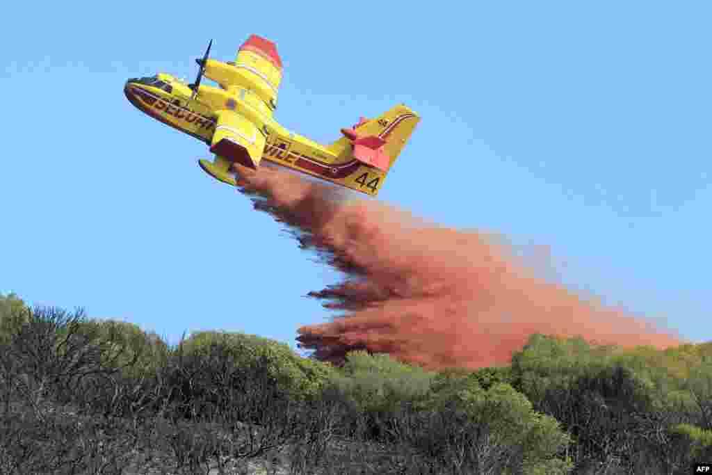 Sebuah pesawat pemadam kebakaran menjatuhkan cairan pemadam kebakaran di Ajaccio, Perancis.