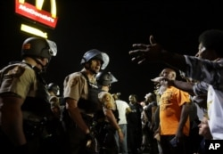 FILE - Officers and protesters face off along West Florissant Avenue in Ferguson, Missouri, Aug. 10, 2015.