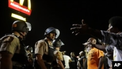FILE - Officers and protesters face off along West Florissant Avenue in Ferguson, Mo., Aug. 10, 2015.