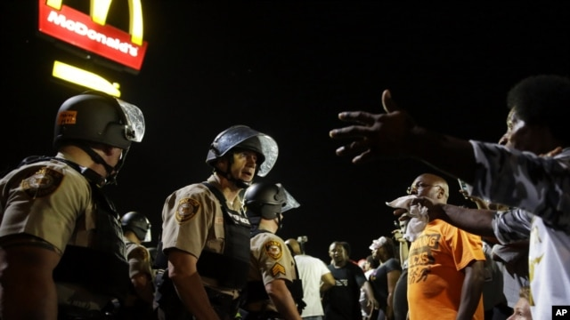 FILE - Officers and protesters face off along West Florissant Avenue in Ferguson, Mo., Aug. 10, 2015. The city and the U.S. Justice Department have reached an agreement over police reform.