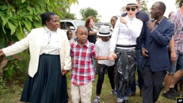U.S. performer Madonna tours Mphandura orpahange with her two adopted children David Banda, second from left, and Mercy James, third from left, near Lilongwe, Malawi, April 5, 2013.