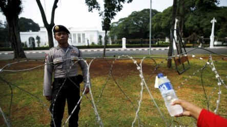 FILE - An Indonesian street vendor offers water to a policeman as he guards in front of the Presidential Palace in Jakarta, Oct. 15, 2015.