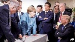 美國總統川普(坐者)6月9日在G7峰會與夥伴國對恃的經典照。