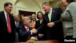El presidente Donald Trump saluda a uno de los invitados a la Casa Blanca durante la firma de la orden ejecutiva sobre la preservación del agua.