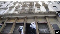 Mutane su na wucewa jikin ginin dake kan titin Park Place a gundumar Manhattan ta New York, wadda Musulmi zasu sake hginawa su maida Masallaci da Cibiyar Al'adu
