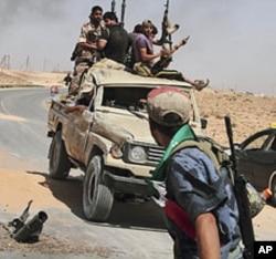 Des rebelles libyens revenant d'un combat non loin de Tripoli