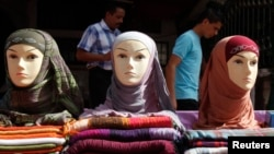 FILE - Men walk past mannequins modelling veils in Tripoli.