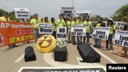 Activists hold placards as they demonstrate against Lynas Corporation to raise questions over the potential environmental hazards arising from radioactive waste, in front of the main entrance of the Lynas factory in Gebeng, 270 kilometers east of Kuala Lu