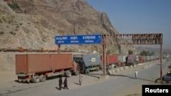 Beberapa orang pria berjalan di dekat papan penunjuk jalan yang menunjukkan jarak menuju beberapa kota di Afghanistan, saat sebuah truk melintasi perbatasan kota Torkham, perlintasan perbatasan Afghanistan-Pakistan (foto: dok).