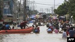 Cư dân lội qua khu vực ngập lụt tại thị trấn Calumpit, tỉnh Bulacan, phía bắc thủ đô Manila, Philippines, ngày 2/10/2011
