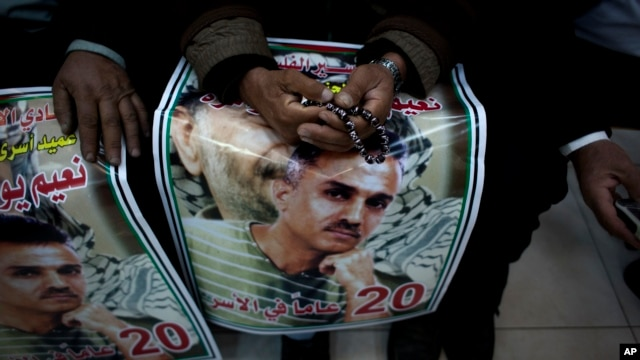 "An elderly Palestinian man holds a poster with a picture of released prisoner Na'em al-Shawamreh and Arabic that reads his name and ""the dean of the released prisoners, 20 years in captivity,"" during celebrations at the Palestinian headquarters, in the We"