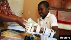 Stevenson Joseph, 12, learns to use a 3-D-printed prosthetic hand at the orphanage where he lives in Santo, near Port-au-Prince, Haiti, April 28, 2014.