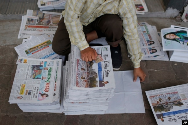FILE - A Bangladeshi worker classifies newspapers, in Dhaka, Bangladesh, Feb. 20, 2016. Under Section 57 of Bangladesh's Information and Communications Technology Act, journalists can be jailed for a variety of offenses, such as defamation, hurting relig