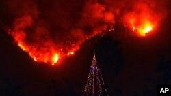 En esta foto proporcionada por el Departamento de Bomberos del Condado de Santa Barbara, con las llamas de fondo se ve un árbol de navidad frente a una casa que debió ser evacuadaen Carpintería, California, el lunes, 11 de diciembre de 2017.